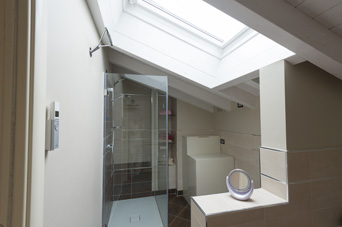 Bathroom with wooden beams and a large skylight